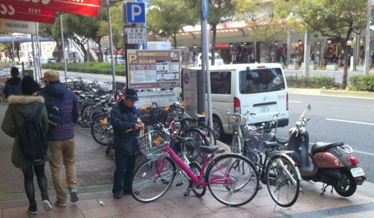 Bicycle and motorbike parking warden issuing warnings (orange notices).  Bicycle parking area behind